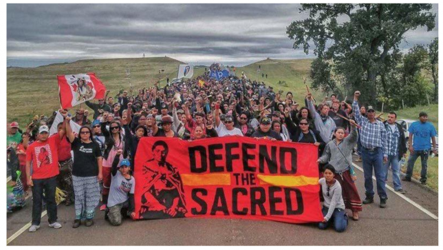 "Protesters hold up a ""Defend the Sacred"" in support of #noDAPL"